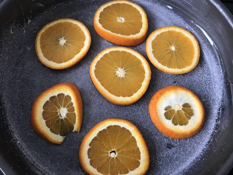 Tranches d'oranges sur le fond du moule beurré et saupoudré de sucre  en poudre